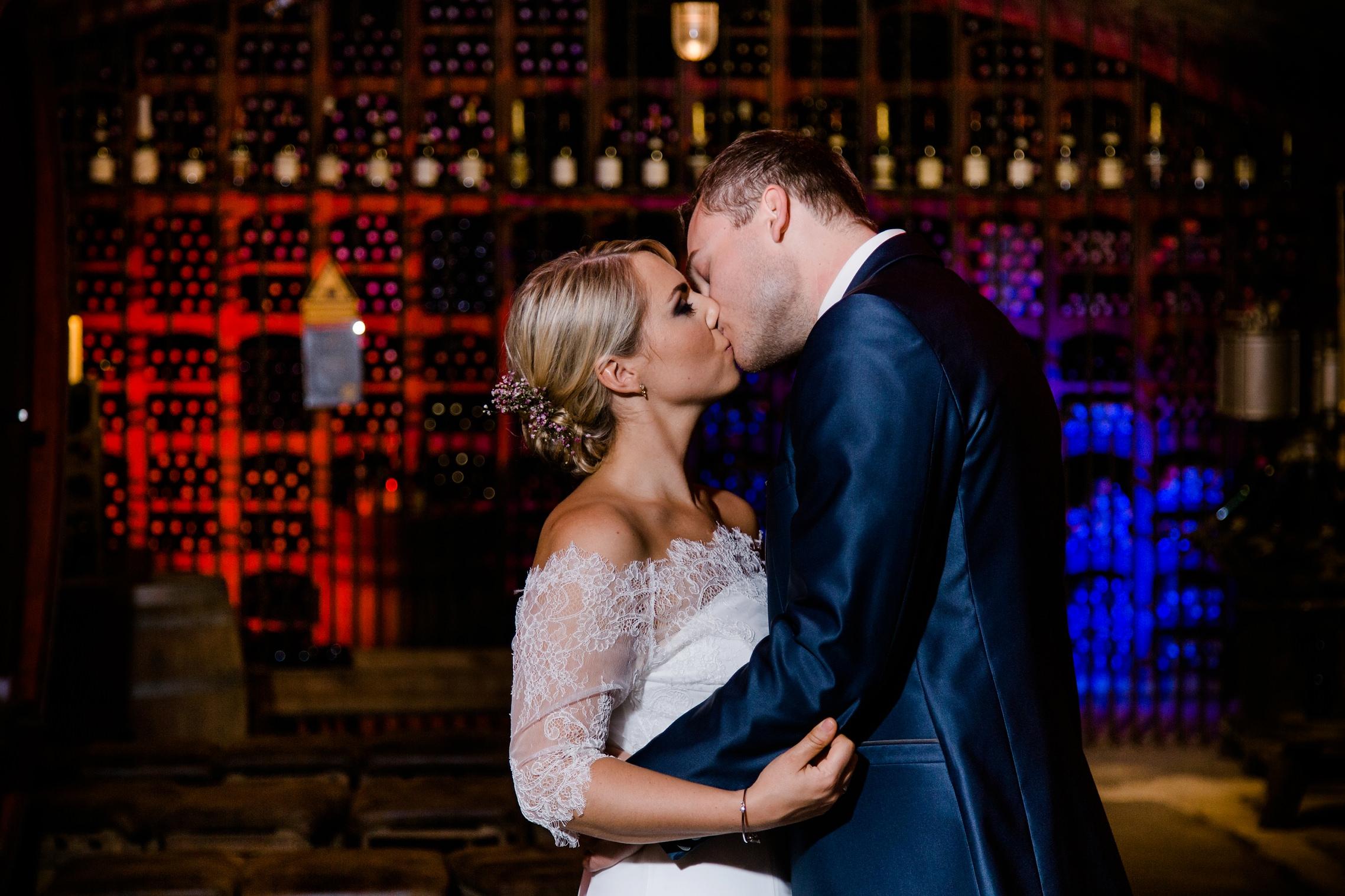 Hochzeits-Shooting im Gewölbe-Weinkeller des Fitz-Ritter in Bad Dürkheim. Im Hintergrund ist ein Flaschenlager mit kräftiger roter und blauer Farbe zu sehen.