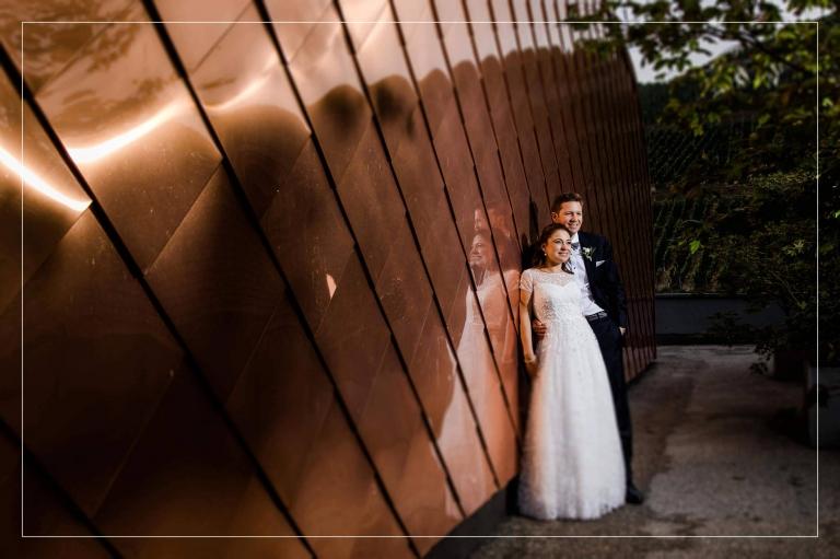 Titelbild zum Blogbeitrag über eine wunderschöne Hochzeit im Gut Hermannsberg - das Brautpaar posiert vor einer Kupferwand.