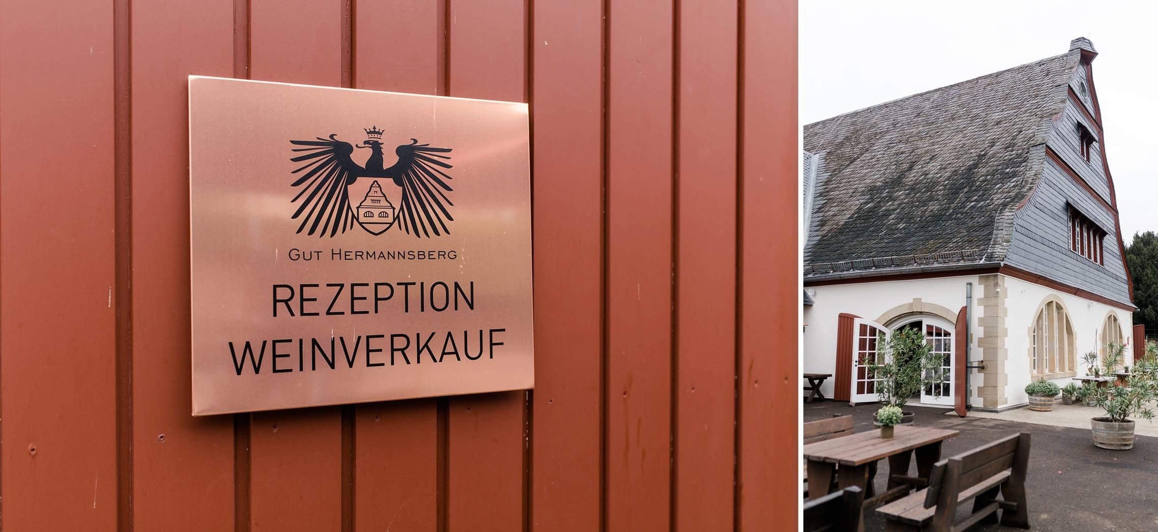 """Ein Schild aus Kupfer auf dem """"Gut Hermannsberg - Rezeption, Weinverkauf"""" steht, sowie das Hauptgebäude des Weingutes."""