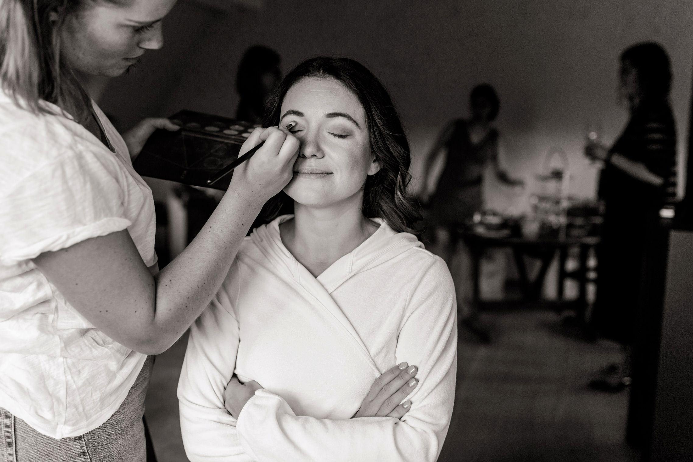 Schwarz-weiss Aufnahme der Braut, die beim Getting Ready im Gut Hermannsberg geschminkt wird.
