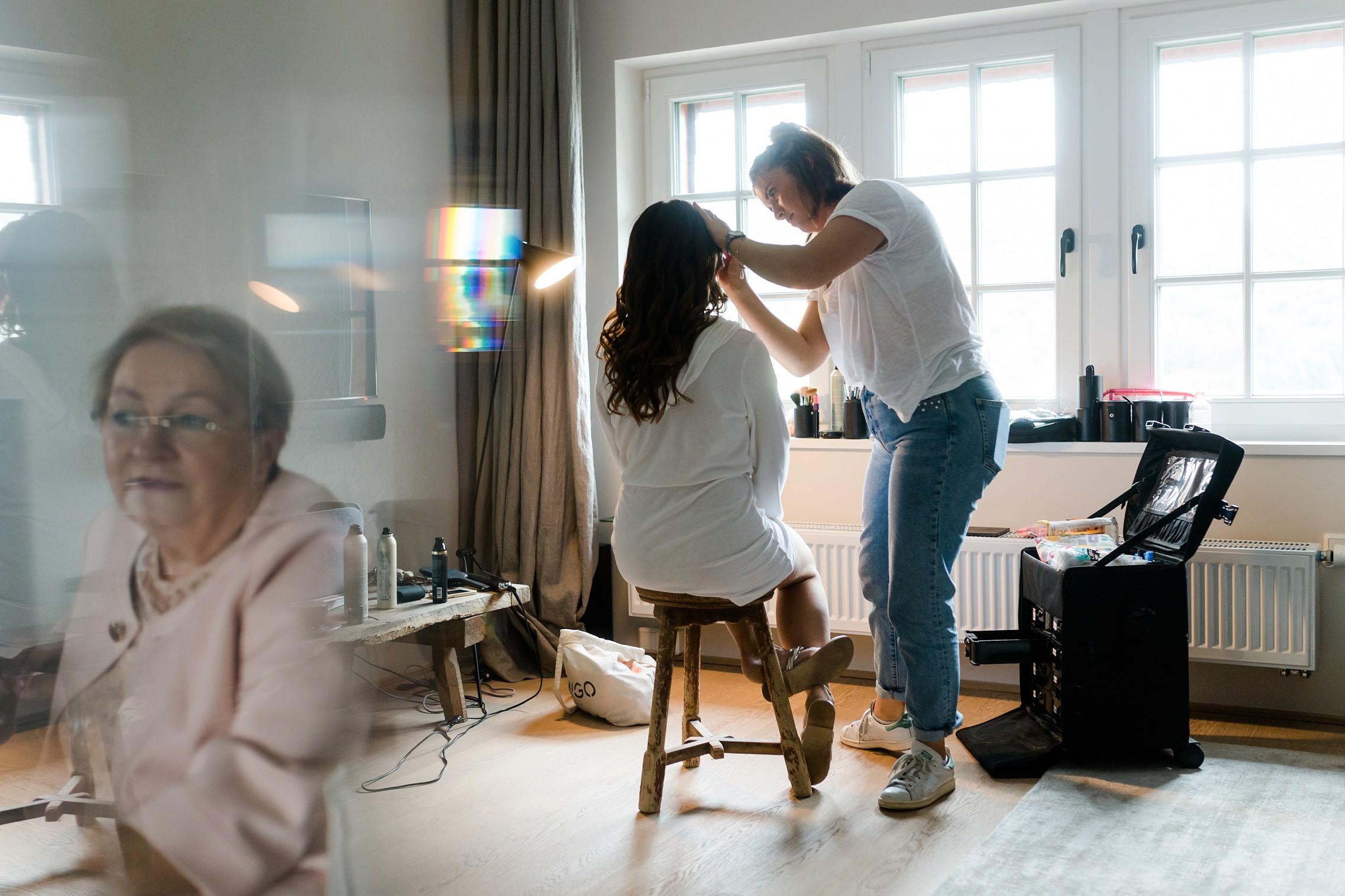 Die Braut wird von einer Verwandten beim Getting Ready beobachtet. Aufnahme mit Spiegeleffekt.
