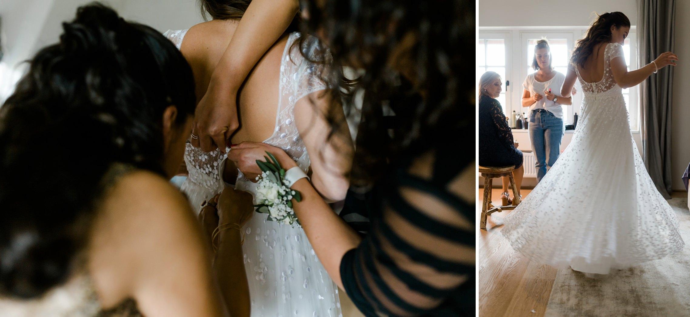Das Brautkleid wird beim Getting Ready im Gut Hermannsberg zugeknöpft und die Braut dreht sich mit dem Kleid im Kreis.