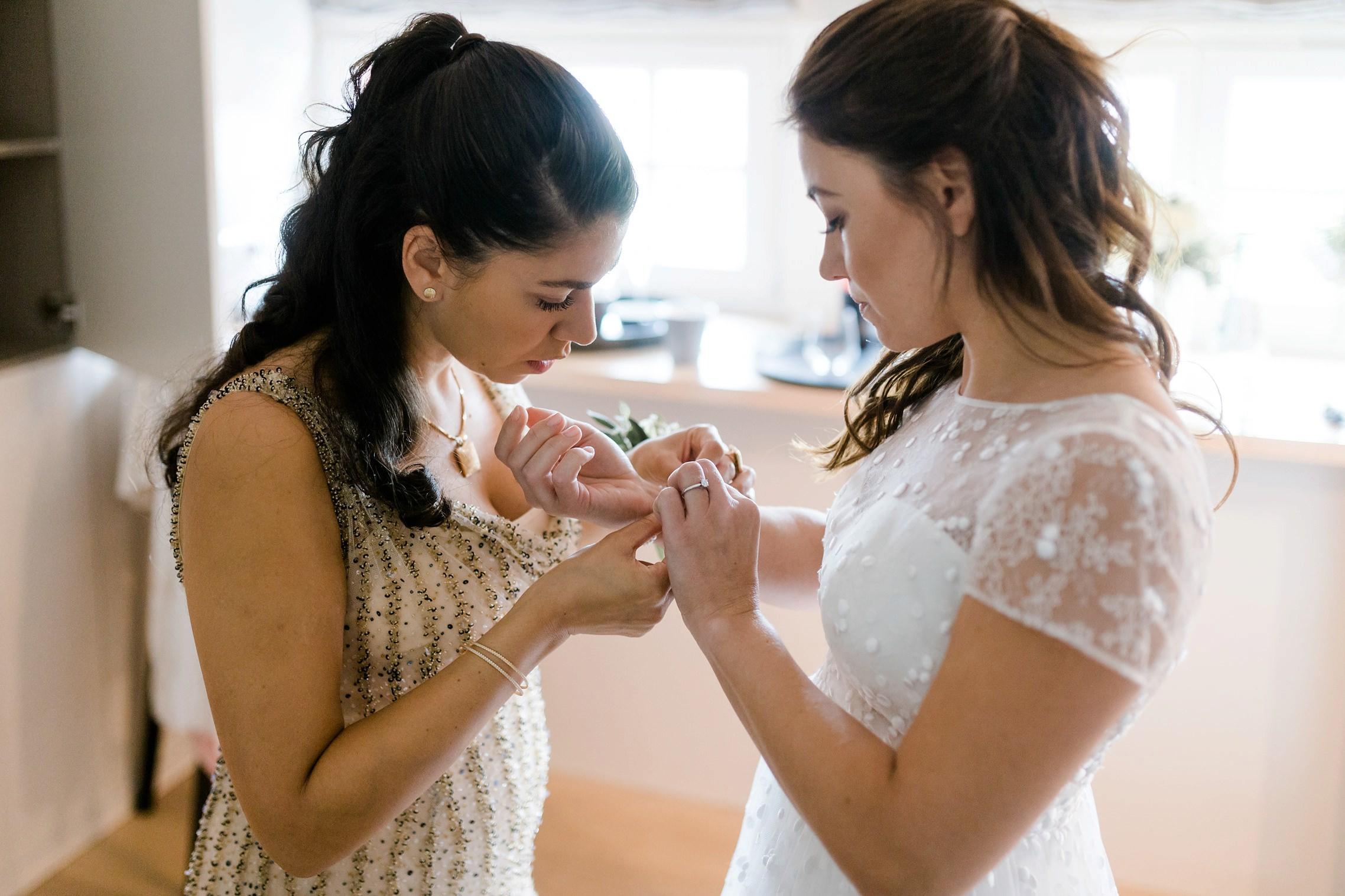 Die Braut und ihre Freundin legen beim Getting Ready der Hochzeit im Gut Hermannsberg den Schmuck an.