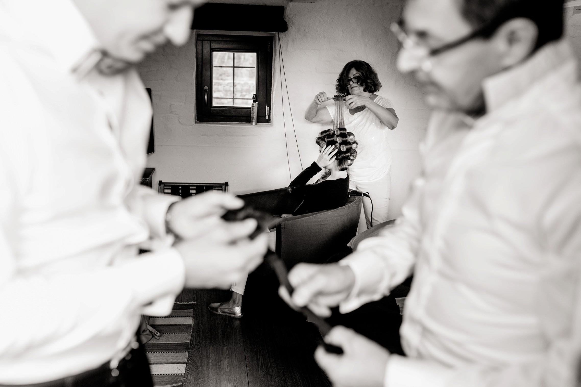 Lustige Szene beim Getting Ready im Gut Hermannsberg: Während die Mutter des Bräutigams der Schwester die Lockenwickler eindreht, beraten Vater und Sohn im Vordergrund über die passende Fliege.