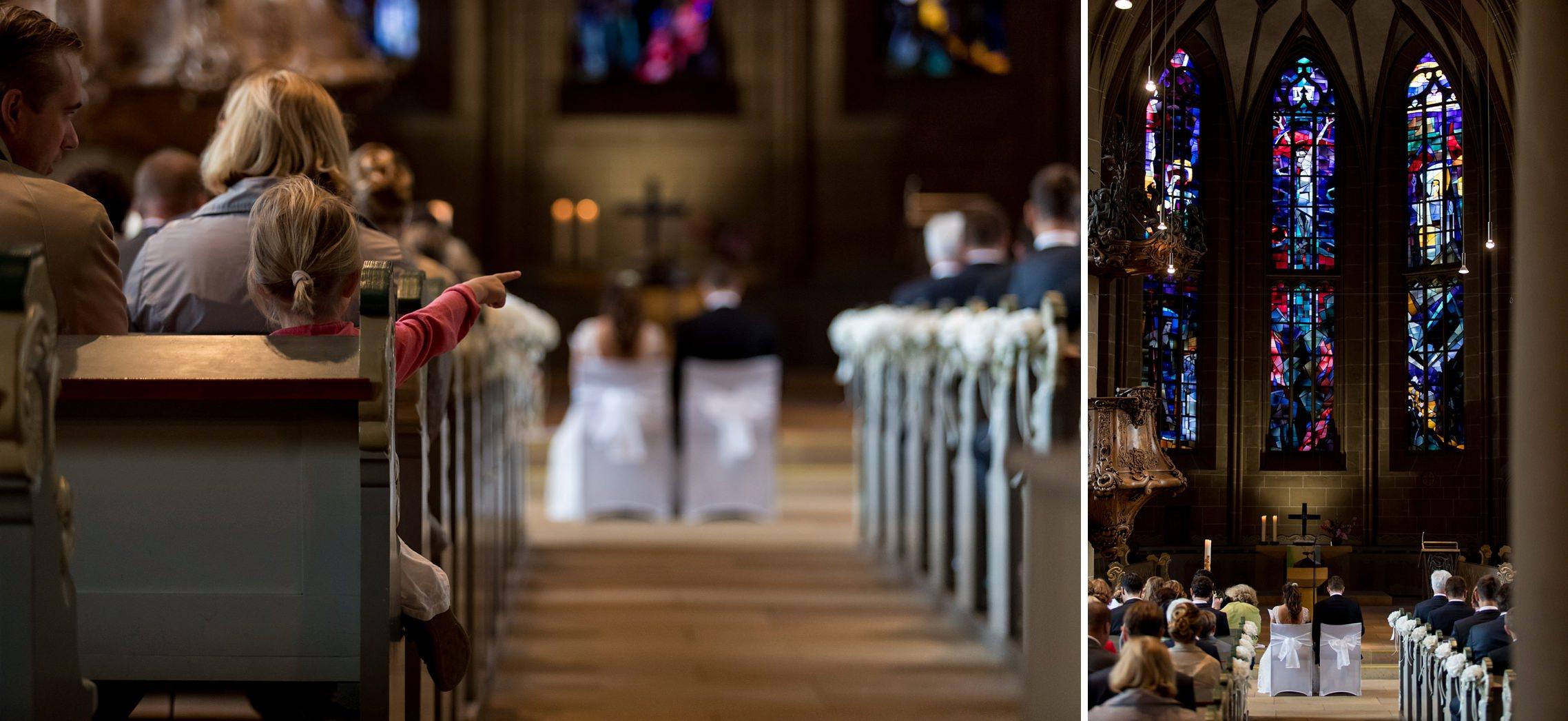 Ein Kind zeigt während des Traugottesdienstes auf das Brautpaar, welches vor großen Buntglasfenstern in der Schlosskirche in Meisenheim sitzt.