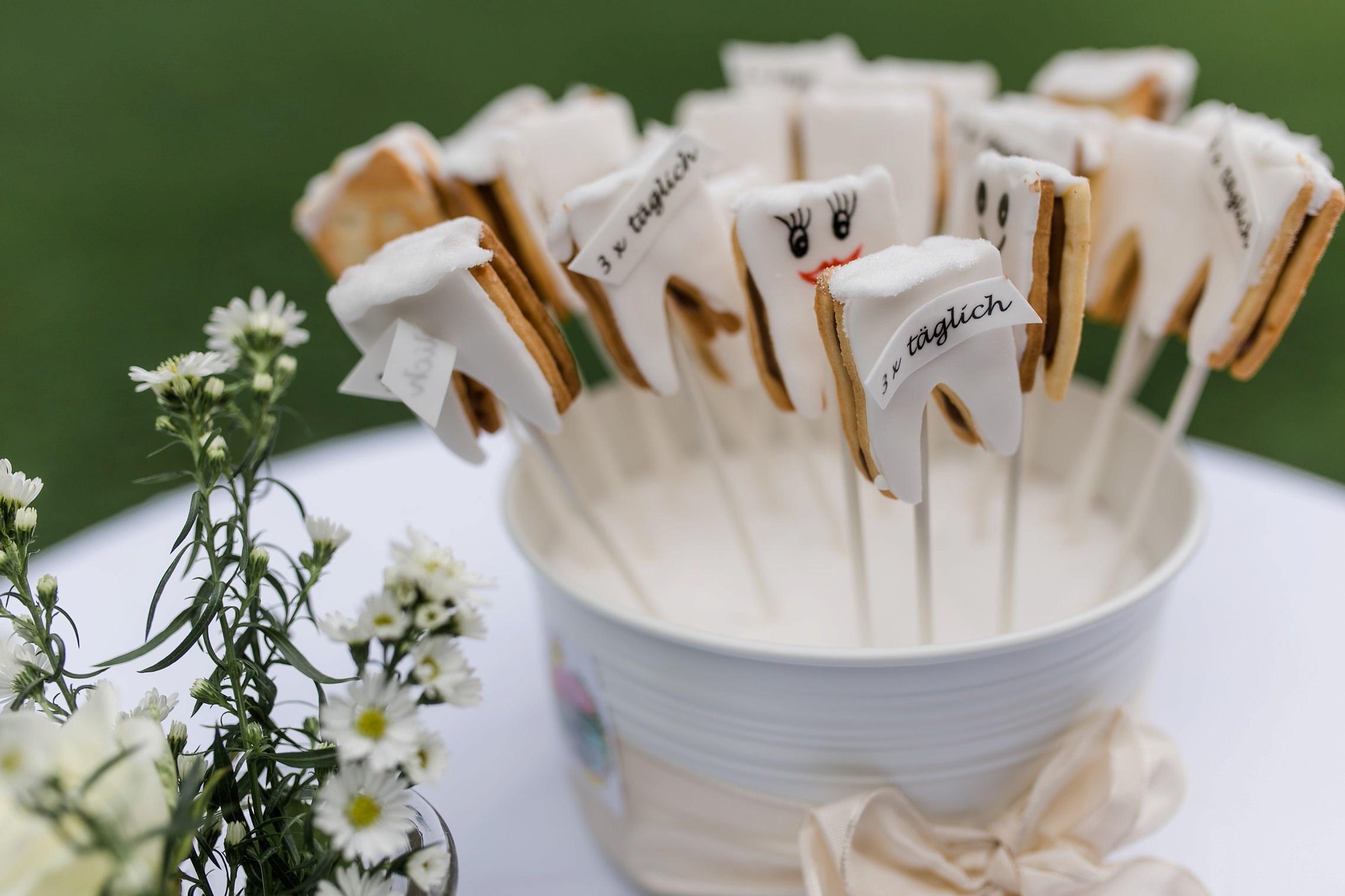 Süßigkeiten in Form von Zähnen auf dem Sektempfang - Braut und Bräutigam sind von Beruf Zahnärzte.
