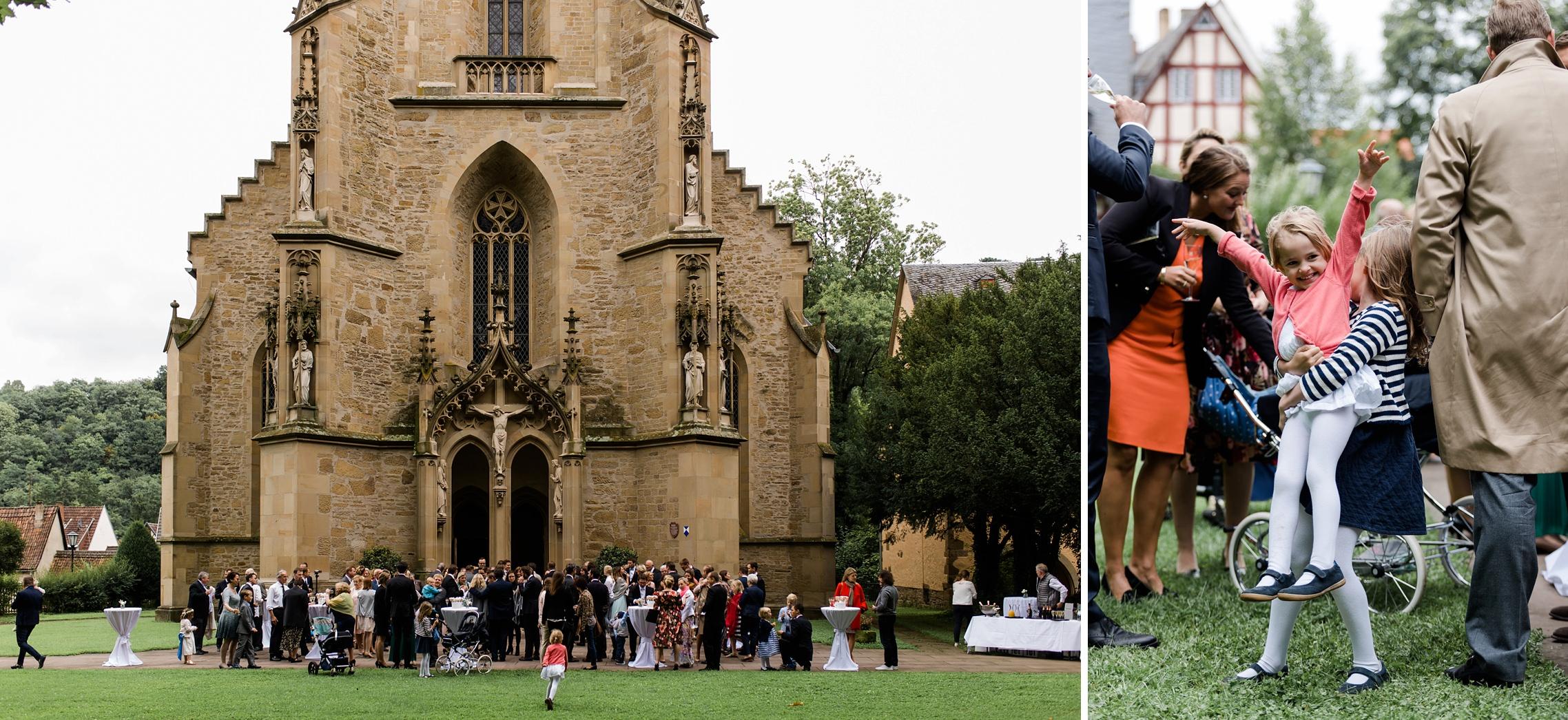 Kinder spielen vor der Schlosskirche in Meisenheim, während die erwachsenen Gäste dem Hochzeitspaar gratulieren.