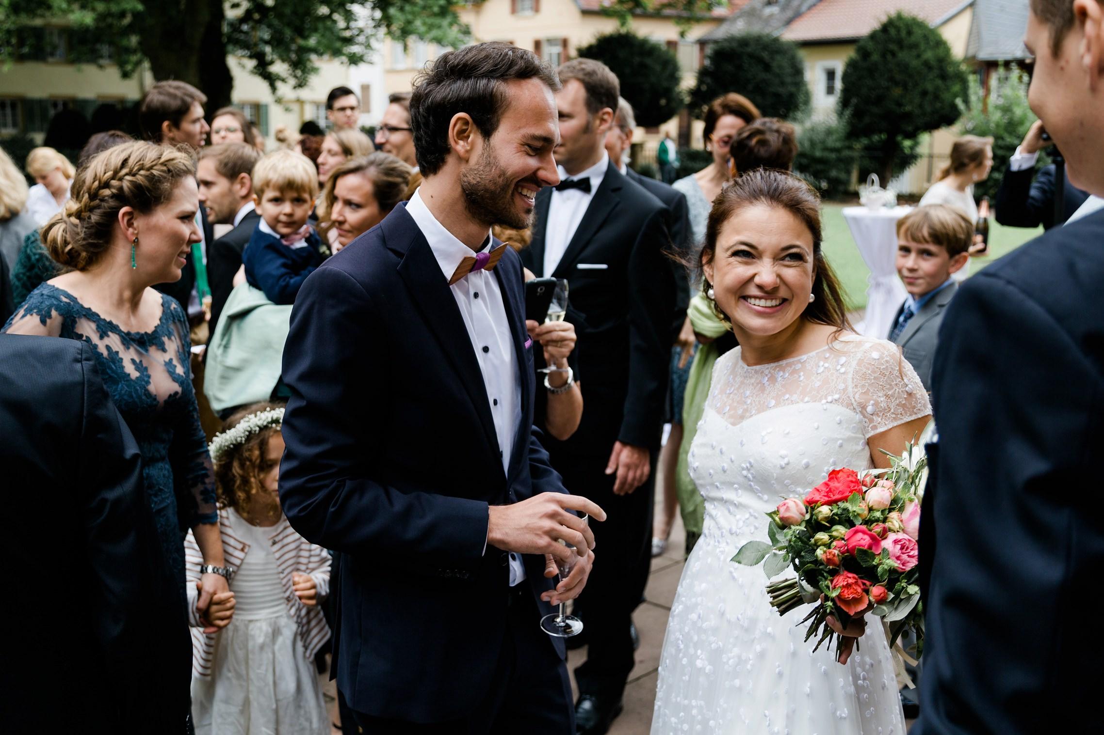 Die Braut strahlt während der Gästegratulationen vor der Schlosskirche in Meisenheim.