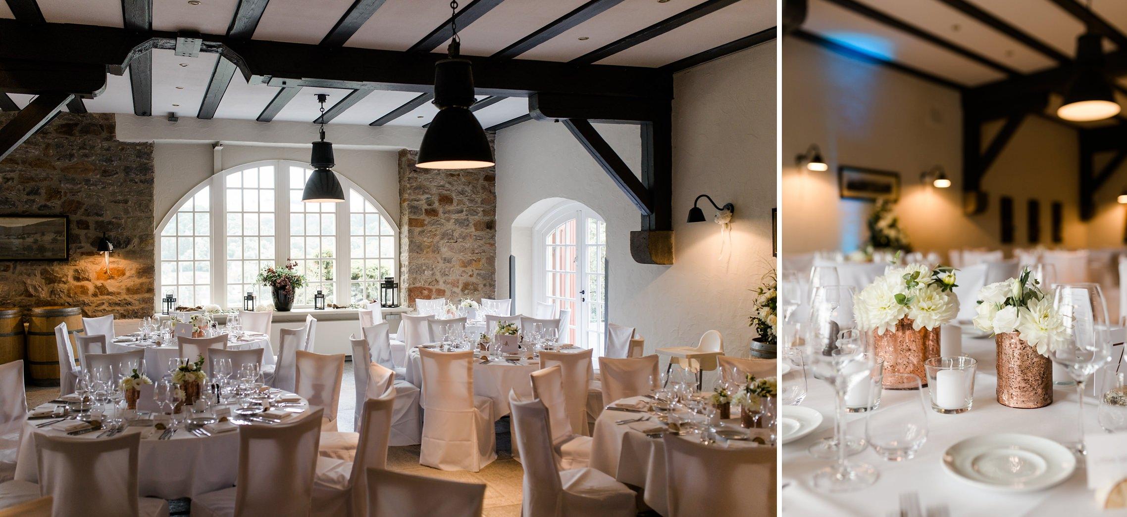 Blick in den festlich gedeckten Saal des Gut Hermannsberg bei einer Hochzeitsfeier.