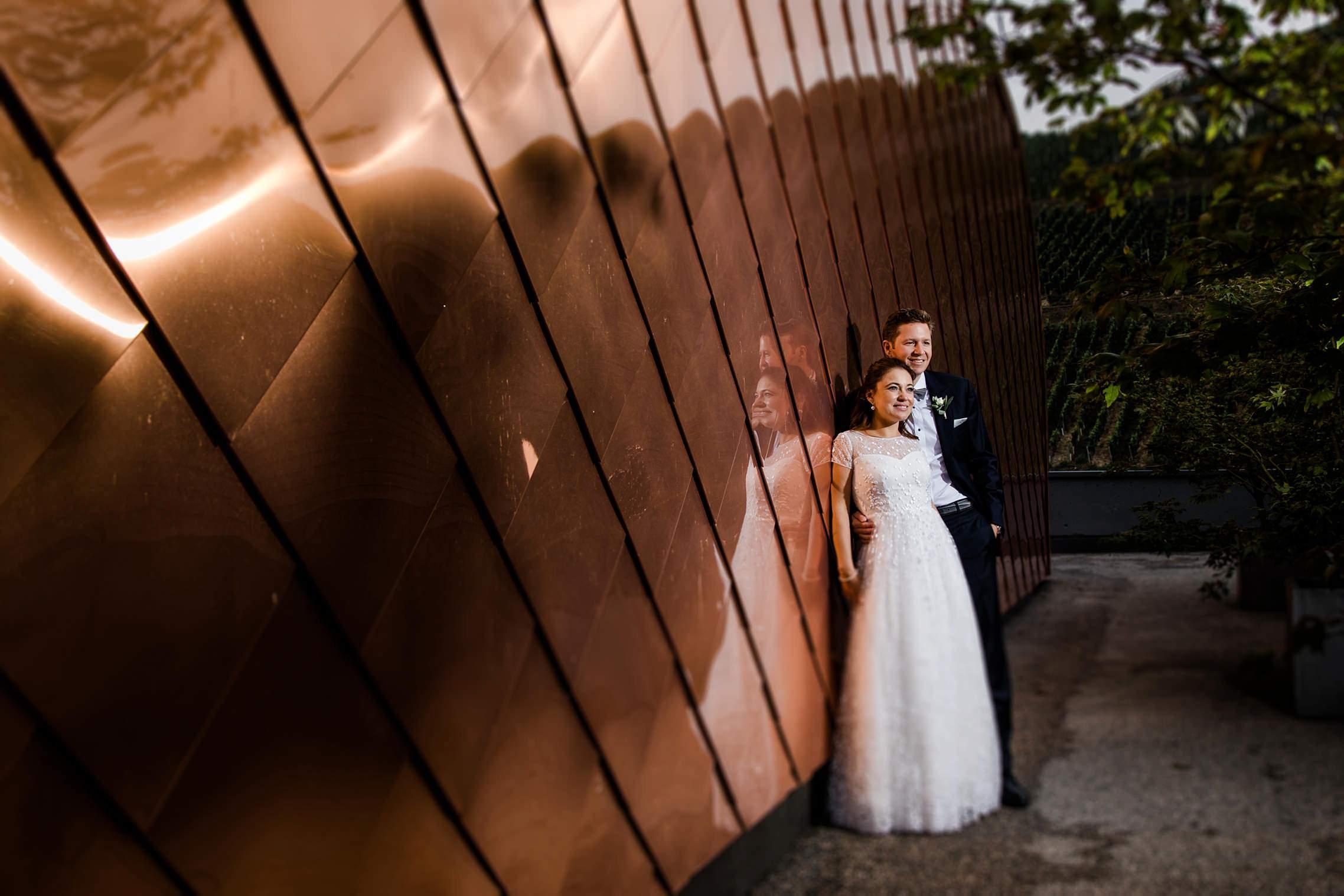 Das Hochzeitspaar posiert vor einer grossen, mit Kupfer beschlagenen Wand, für das Shooting der Hochzeit im Gut Hermannsberg.