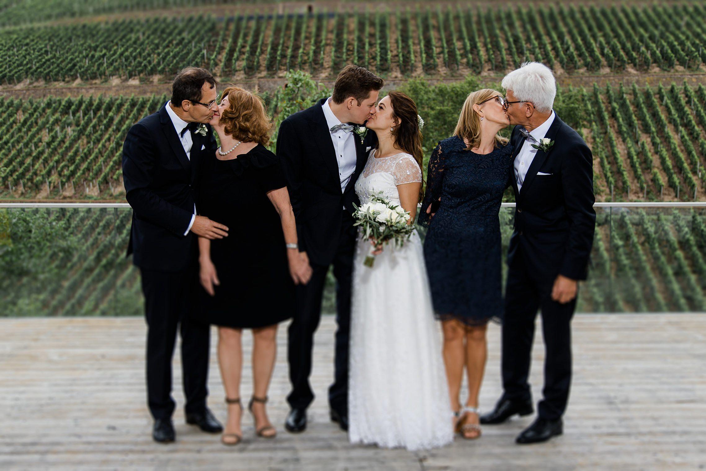 Lustiges Familienbild: die Eltern des Brautpaares küssen sich zeitglich mit dem Hochzeitspaar auf dem Gut Hermannsberg.