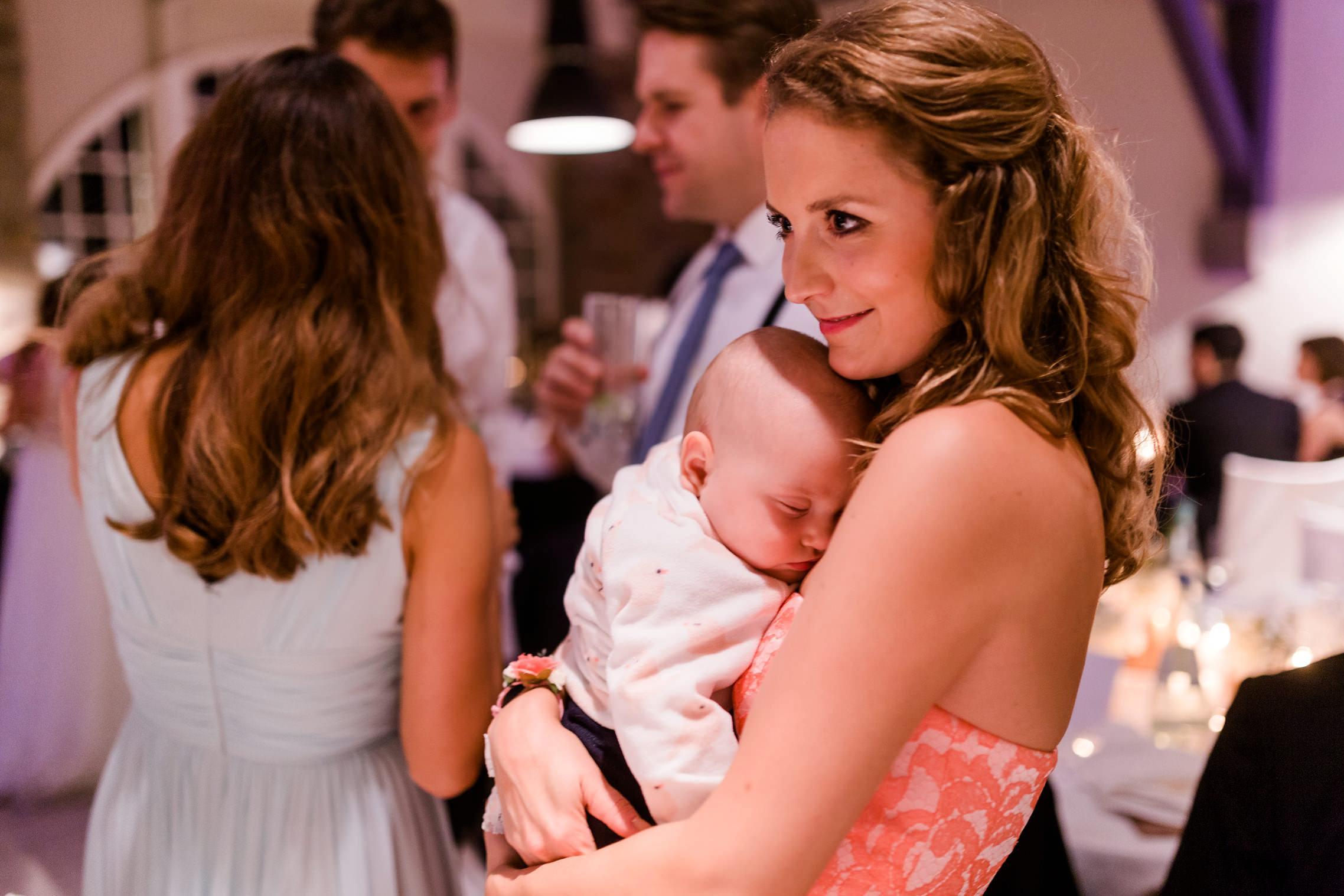 Eine Frau hält ein schlafendes Baby im Arm.