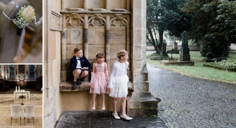 Blumenkinder warten vor Eingangsportal der Kirche und beobachten den Regen