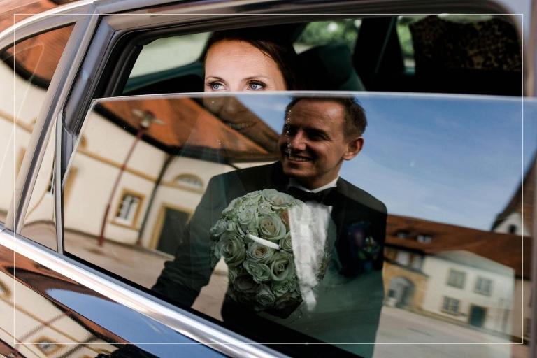 Bräutigam spiegelt sich im Autofenster, Braut schaut ihn verliebt an.