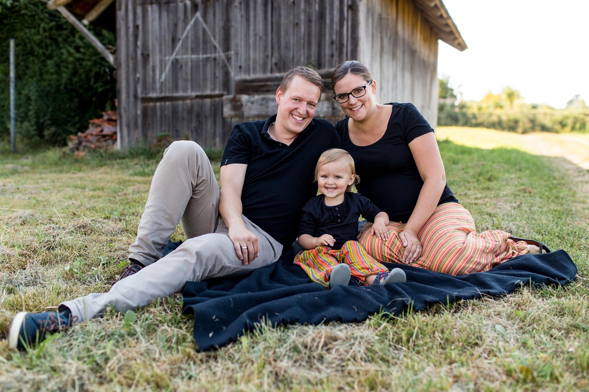 Eltern sitzen mit Tochter auf Decke