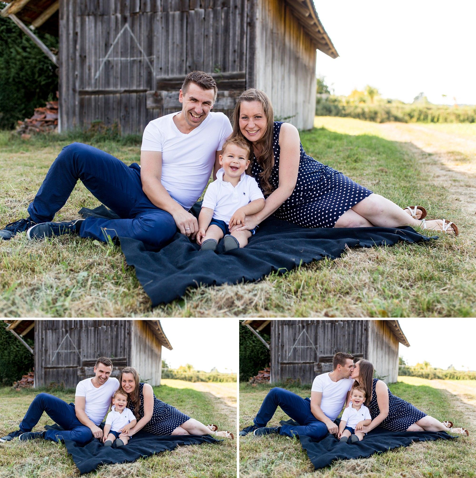 Eltern sitzen mit ihrem Sohn auf Decke