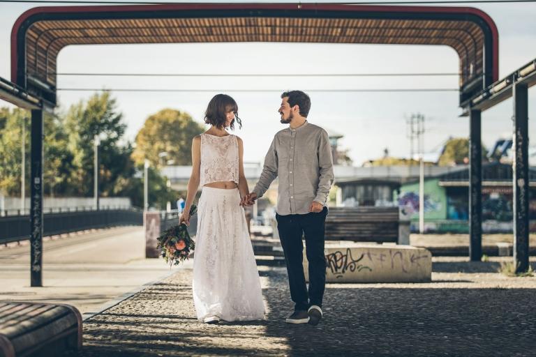 Braut und Bräutigam spazieren im Jungbusch Mannheim unter einem Holzdach