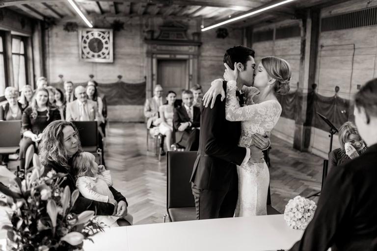 Emotionaler Kuss des Brautpaares von Müttern eingerahmt