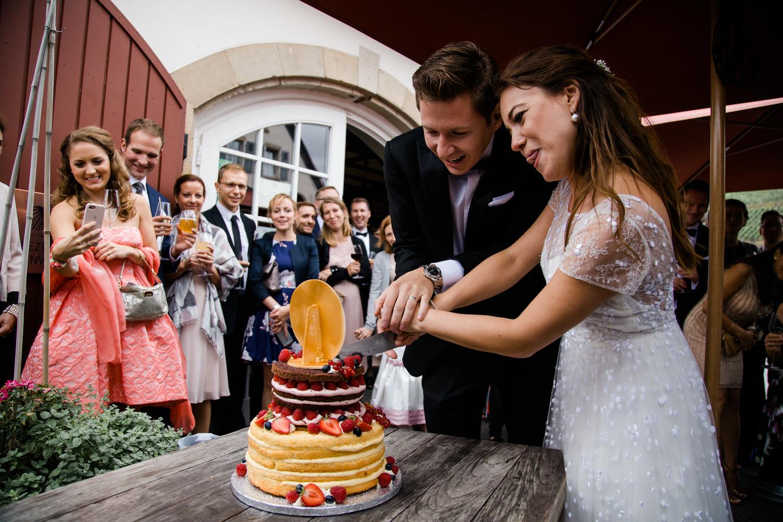 Lustiges Hochzeitspaar schneidet die Hochzeitstorte bei der Hochzeitsreportage an